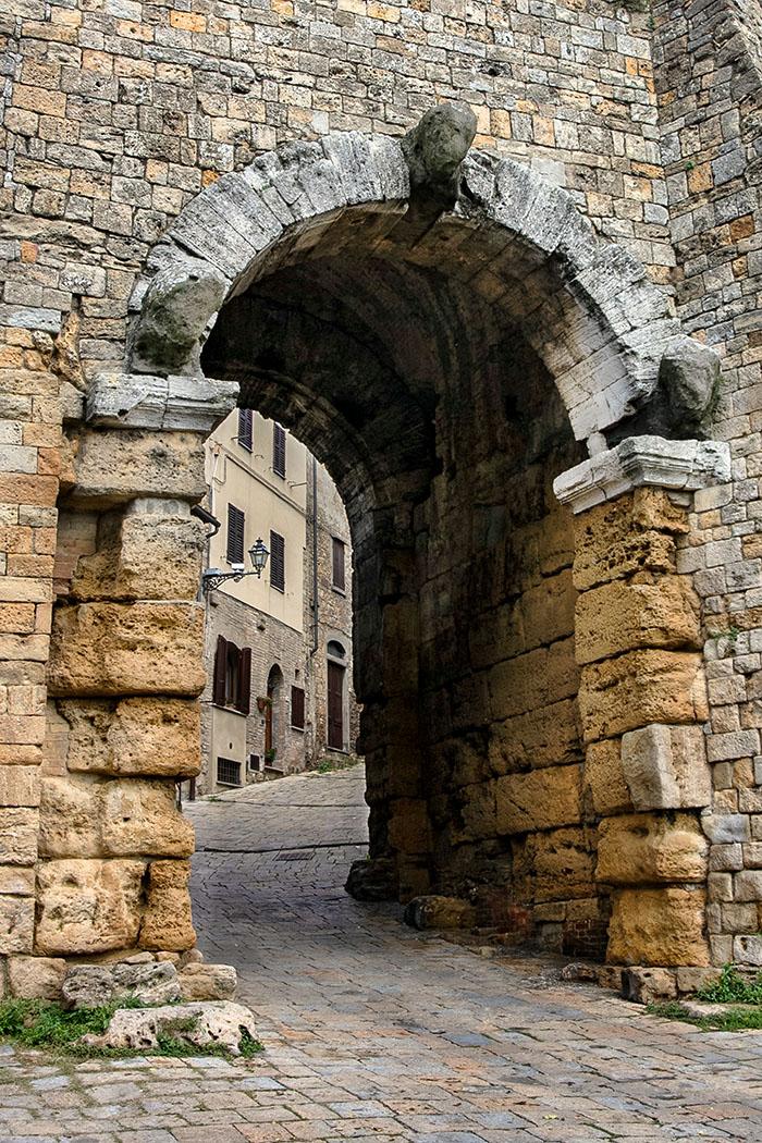 Toskana: Cicero und die etruskische Familie Caecina aus Volterra - reise-zikaden.de, italy, italien, tuscany, toskana, volterra, Porta all'Arco - Die Porta all'Arco ist das Wahrzeichen Volterras und das älteste erhaltene etruskische Stadttor. Der untere Bereich aus großen Quadern stammt aus dem 4. Jhd. v. Chr. Bögen und Tonnengewölbe wurden etwa hundert Jahre später errichtet. Die drei Köpfe stellen die Schutzgötter des etruskischen Felathri dar: Tinia (Zeus), Uni (Hera) und Menvra (Minerva) dar.