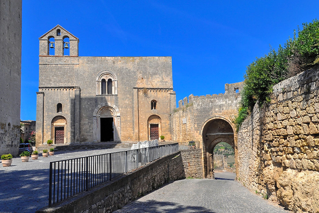 Die romanische Kirche Santa Maria in Castello in Tarquinia wurde 1121 begonnen und liegt nahe vom Stadttor. Schön verziertes Hauptportal mit Cosmatenschmuck.