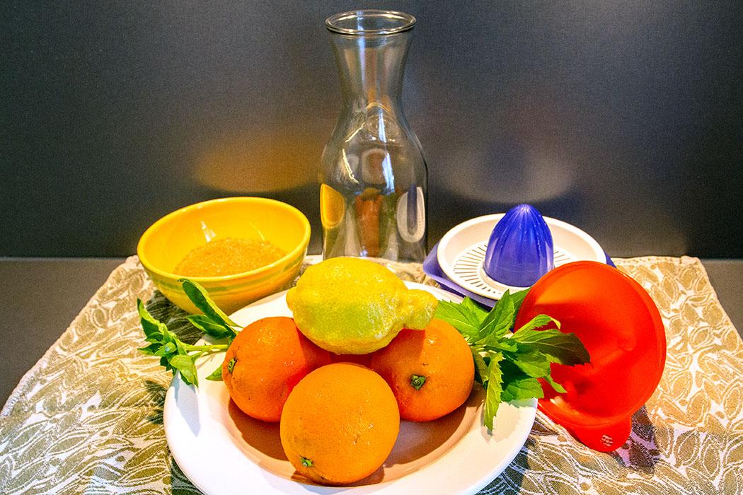 Die Zutaten für einen fruchtigen Orangen-Zitronen-Sirup sind simpel: Orangen- und Zitronensaft und Zucker.