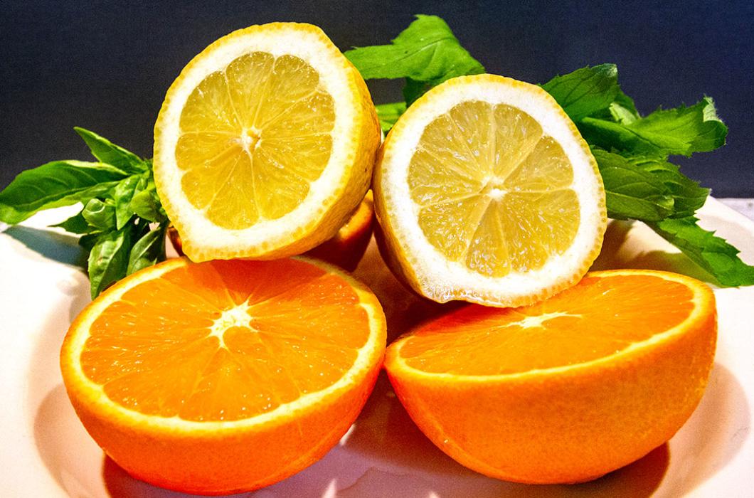 Frische Bio-Orangen und Zitronen halbieren.
