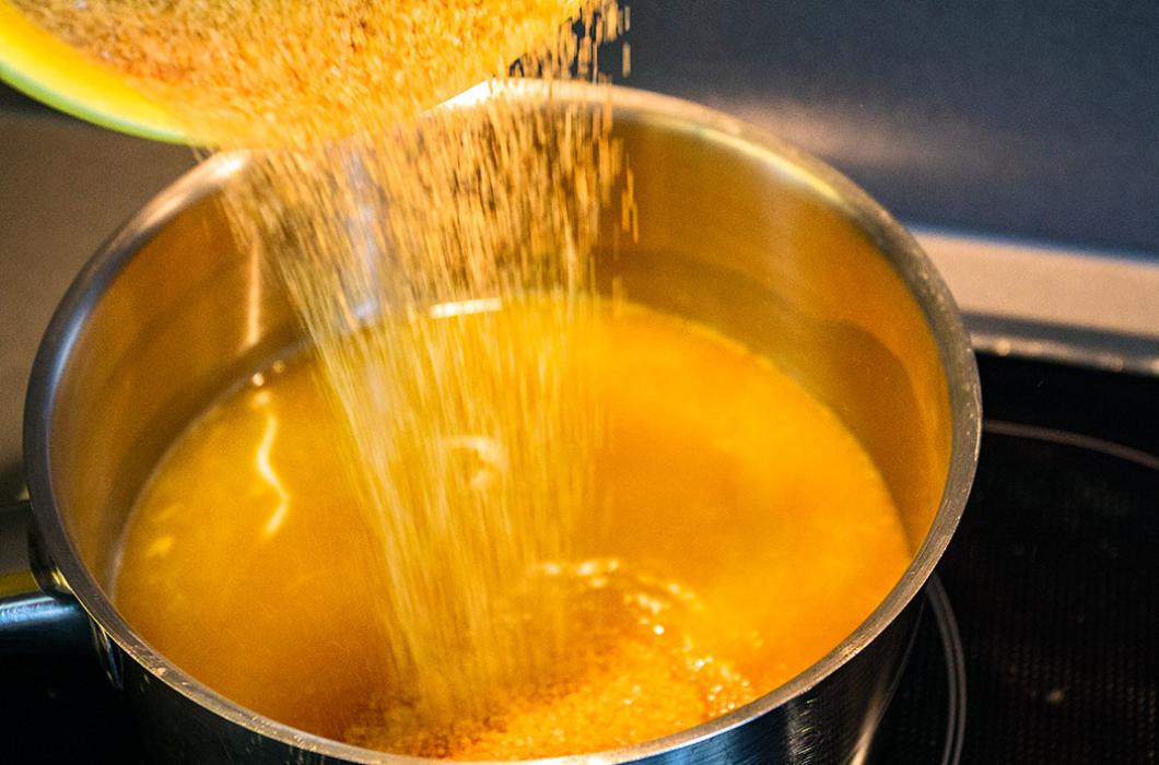 Rohrzucker zum Zitrussaft in einen Topf geben und langsam aufkochen lassen.