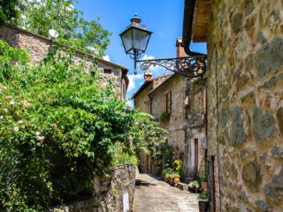 Italien wie im Bilderbuch: Idyllische Gassen geschmückt mit blühenden Blumentöpfen, daneben gepflegte schattige Gärten.