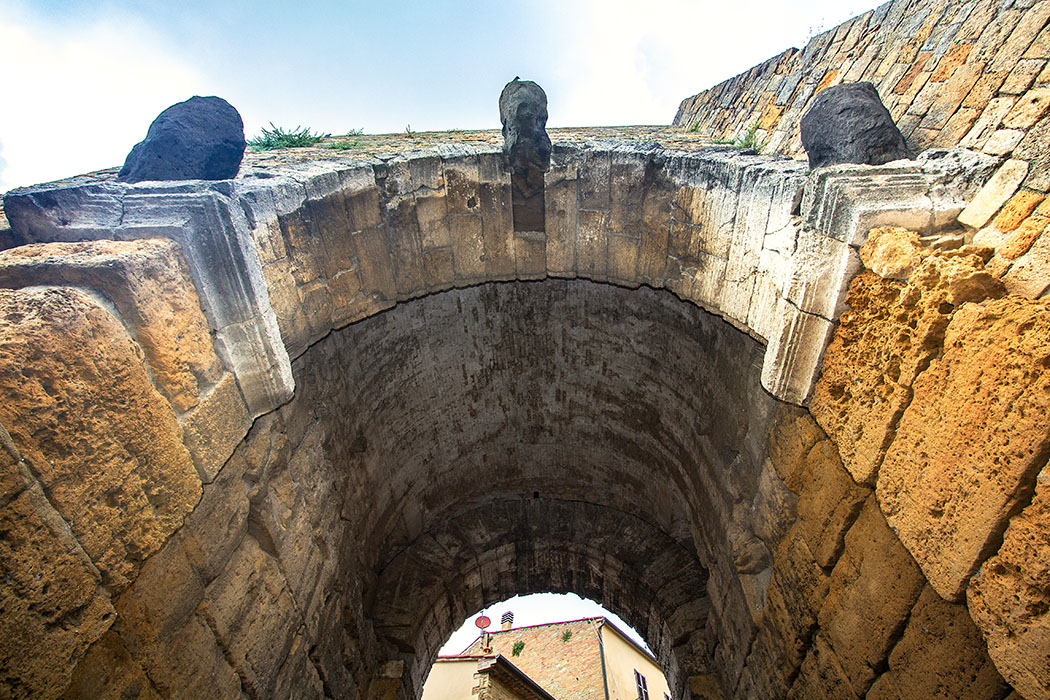 """Volterra: Porta all'Arco – Das älteste etruskische Stadttor Italiens - reise-zikaden.de, Italy, Tuscany, Volterra, Porta all'Arco, Godheads - Die Porta all'Arco belegt, dass die Etrusker nicht nur das """"falsche"""" Kraggewölbe errichteten konnten, sondern auch die Anlage des aus Keilsteinen erbauten """"echten"""" Gewölbes beherrschten."""