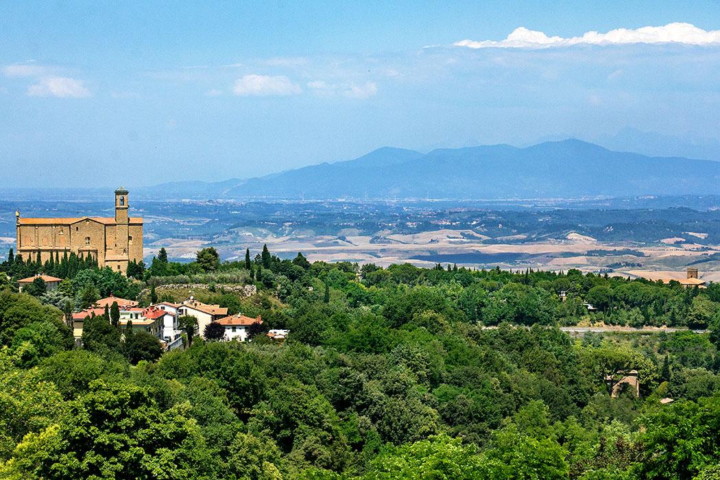 Volterra: Die Geschichte von San Giusto und der Badia-Nekropole - reise-zikaden.de, Italy, Tuscany, Volterra, San Giusto Nuovo, San Giusto in Botro - Oberhalb vom antiken Theater in Volterra bietet sich eine fantastische Aussicht auf die Kirche San Giusto Novo (links) und der Abtei Badia Camaldulense (am rechten Bildrand). Im Hintergrund ist der Apennin und die Apuanischen Alpen zu sehen.