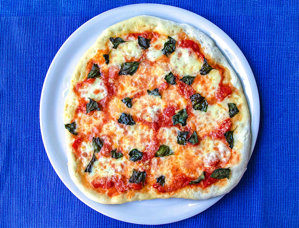 """Pizza Margherita: Den Klassiker aus Italien selber machen - reise-zikaden.de, Pizza Margherita Der Klassiker aus Italien, Rezept - Die besten Ergebnisse für Pizza Margherita werden Zuhause mit einem Pizza-Stein erzielt. Doch auch auf einem Backblech können Pizzen gut gelingen. Dazu sollte Paniermehl als """"Unterlage"""" verwendet werden."""