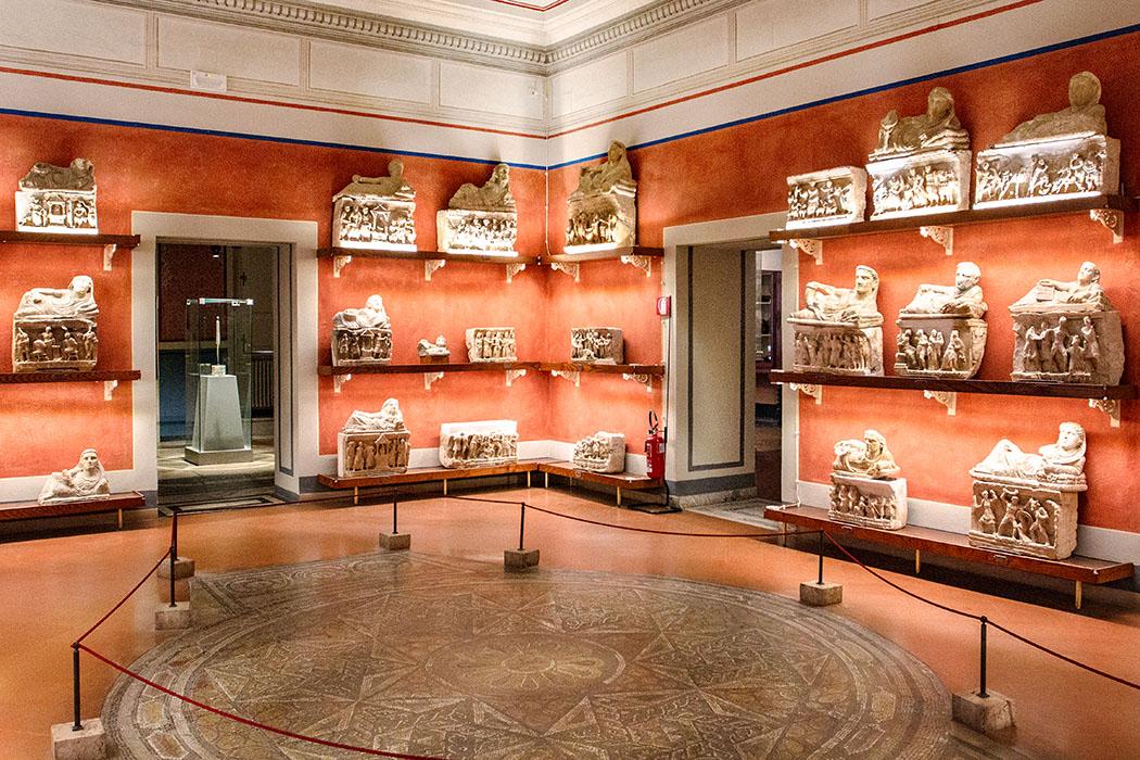 Toskana: Volterra – 14 Sehenswürdigkeiten aus der Zeit der Etrusker - reise-zikaden.de, Volterra, Urn, Guarnacci-Museum, Room XIII , roman mosaic, etruscan urns, Ombra della Sera - Im ersten Stock des Guarnacci-Museums in Volterra erwartet den Besucher einer der schönsten Ausstellungsräume. Die Mitte nimmt ein römisches Rundmosaik ein, das aus den Thermen von San Felice stammt. In den Wandregalen stehen Dutzende Urnen mit Liegefigur und Reliefs, diese Motive zeigen griechischen Mythen. Datierung: 3. Jhd. v. Chr.