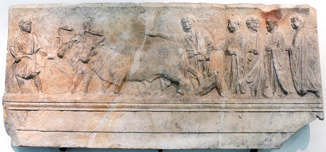 """Sulcus primigenius_Museo Archeologico Nazionale Aquileia_01 - Die römische Reliefplatte zeigt den Ritus """"Sulcus primigenius"""": Ein Gespann mit zwei Rindern zieht einen Pflug. Ein Arbeiter hält das Zaumzeug, ein weiterer führt die Zugtiere. Dem Pflug folgen vier Magistrate in Toga. Die Marmorplatte war im Amphitheater von Aquileia verbaut und befindet sich Museo Archeologico Nazionale Aquileia. Foto: Wikipedia, Wolfgang Sauber"""
