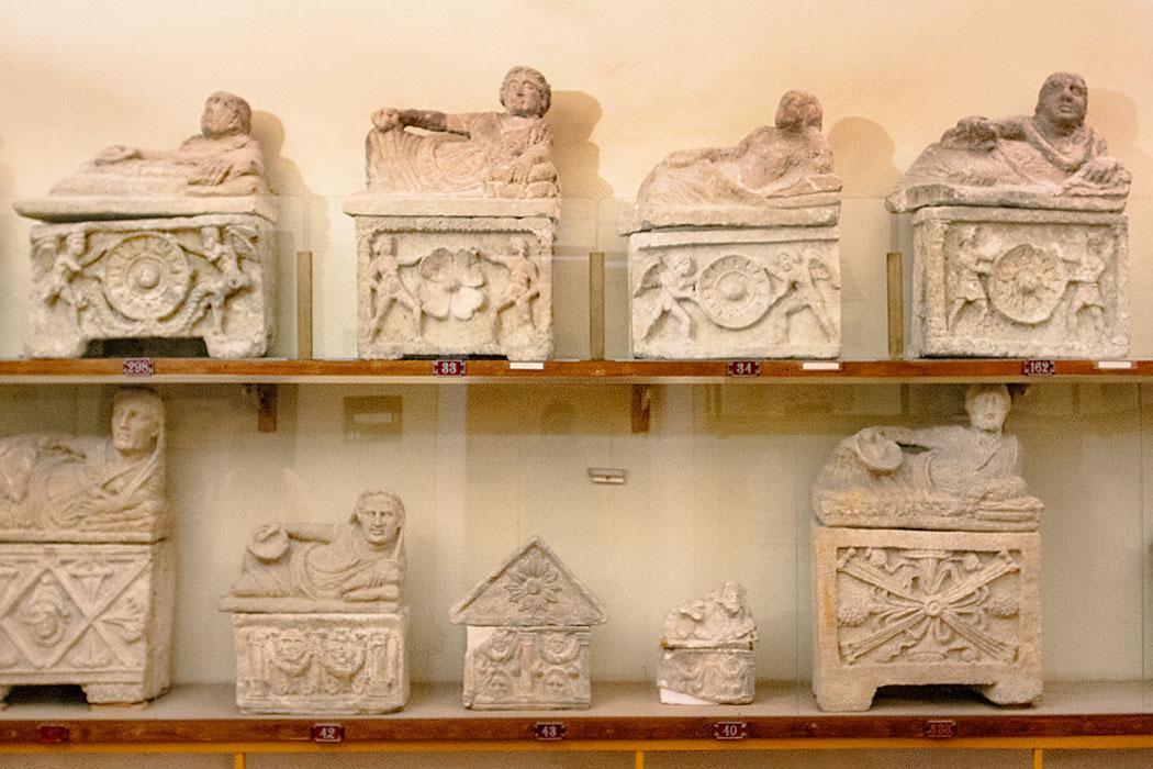 """reise-zikaden.de, italy, tuscany, volterra, museum guarnacci, etruscan urns - Volterra, Archäologischen Museum Guarnacci: Im Saal """"Demoni, Maschere e Simboli"""" (Dämonen, Masken und Symbole) bekommt der Besucher einen guten Eindruck vom Aussehen etruskischer Relief-Urnen."""
