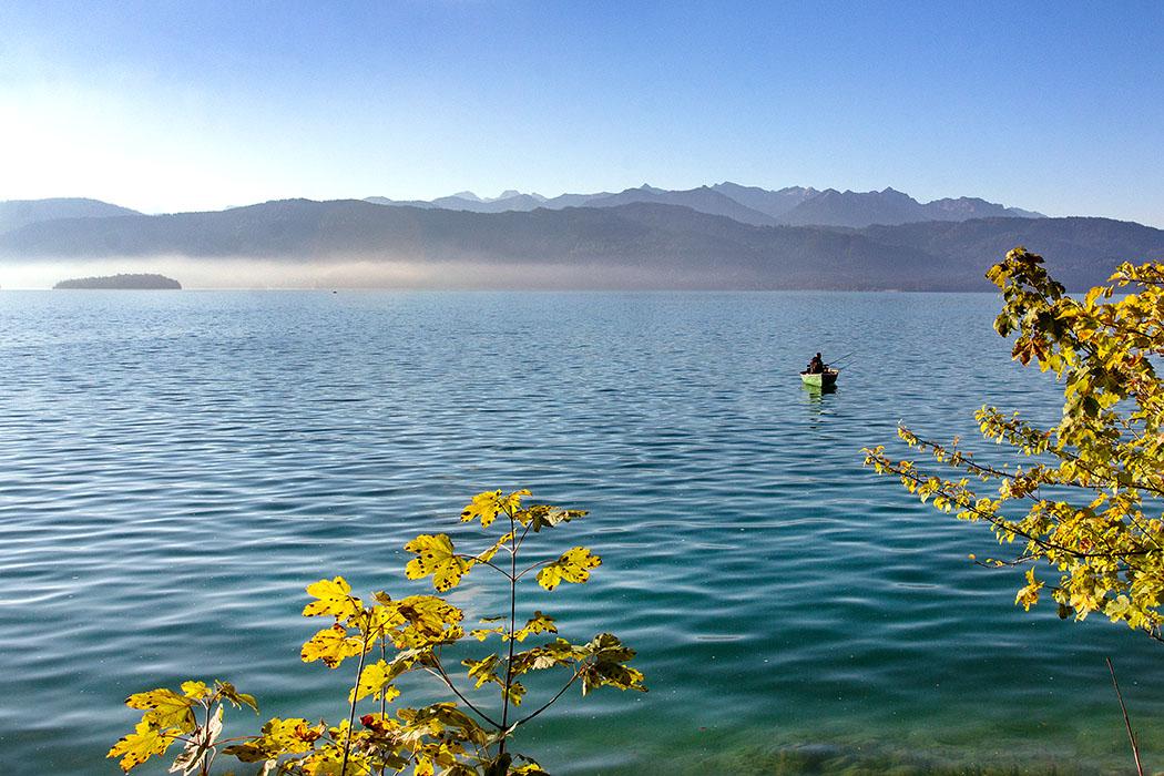 reise-zikaden.de, oberbayern, urfeld, walchensee, angler - Die Anfahrt nach Wallgau und zum Oberen Isartal im Karwendel führt über den Walchensee. Am frühen Morgen steht der Dunst über dem See und der Insel Sassau, ein Angler ist in seinem Boot unterwegs.