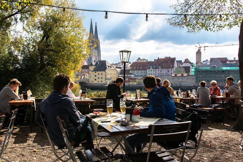 """reise-zikaden.de, oberpfalz, donau, regensburg, obere woehrd, alte linde, biergarten - Vom Biergarten im empfehlenswerten Gasthof """"Alte Linde zur Steinernen Brücke"""", auf der Donauinsel Obere Wöhrd, bietet sich der schönste Blick auf die Altstadt von Regensburg. Entdeckungstouren in Regensburg - 25 historische Highlights"""