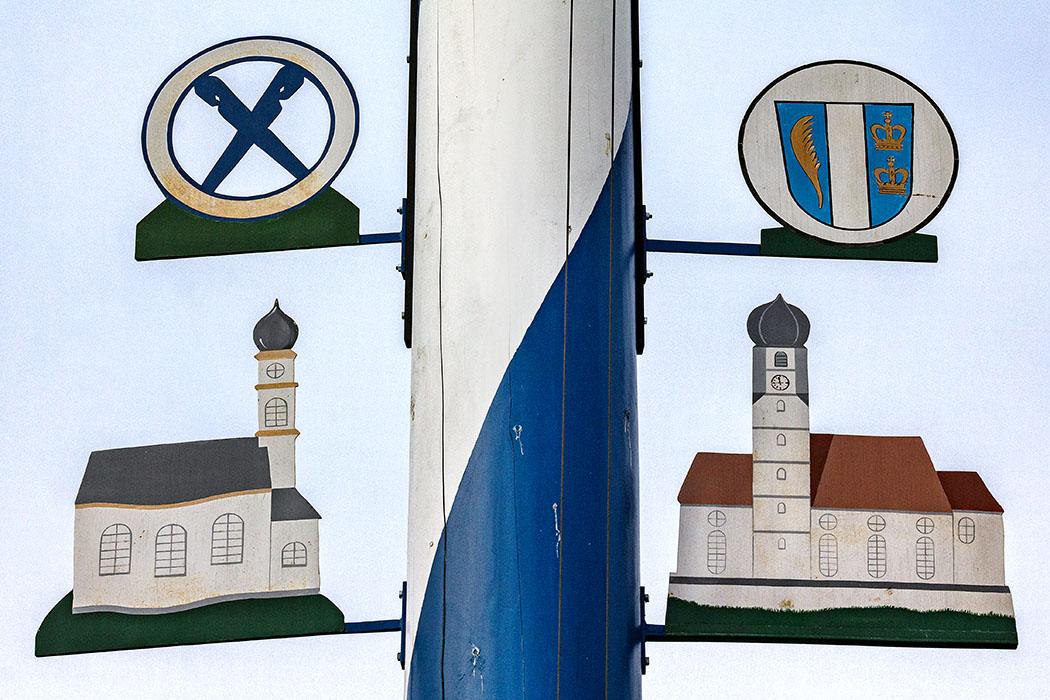 Der Maibaum von Kleinhelfendorf zeigt die beiden St. Emmeram geweihten Kirchen. Die Marterkapelle (links) und die Pfarrkirche. Das Wappen zeigt in der Mitte die Römerstraße, der Palmzweig ist ein Symbol für das Martyrium von Emmeram, die beiden Kronen verweisen auf den Königshof.
