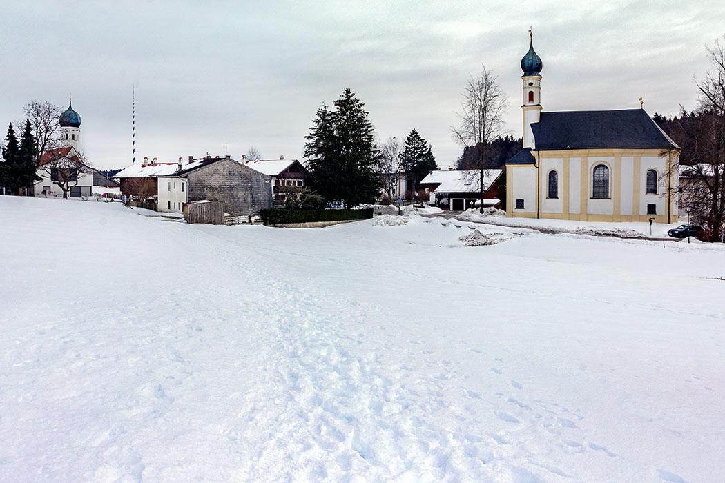 Blick auf Kleinhelfendorf von Nordwesten. Der Standpunkt befindet sich an der Römerstraße Via Julia nach Salzburg. Die Militärstraße wurde während der römischen Kaiserzeit im 2. und 3. Jhd. erbaut und bis ins Mittelalter genutzt.