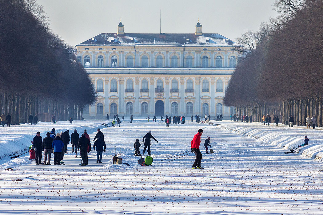 Winter in München & Umgebung: 18 Spaziergänge und Ausflüge - schleissheim_schloss_winter - Was für eine Kulisse für einen Winterspaziergang! Der Blick am Mittelkanal auf das Neue Schloss Schleißheim zeigt die schönsten Seiten des Winters: Eisstockschießen, Langlaufen und Spaziergänger.