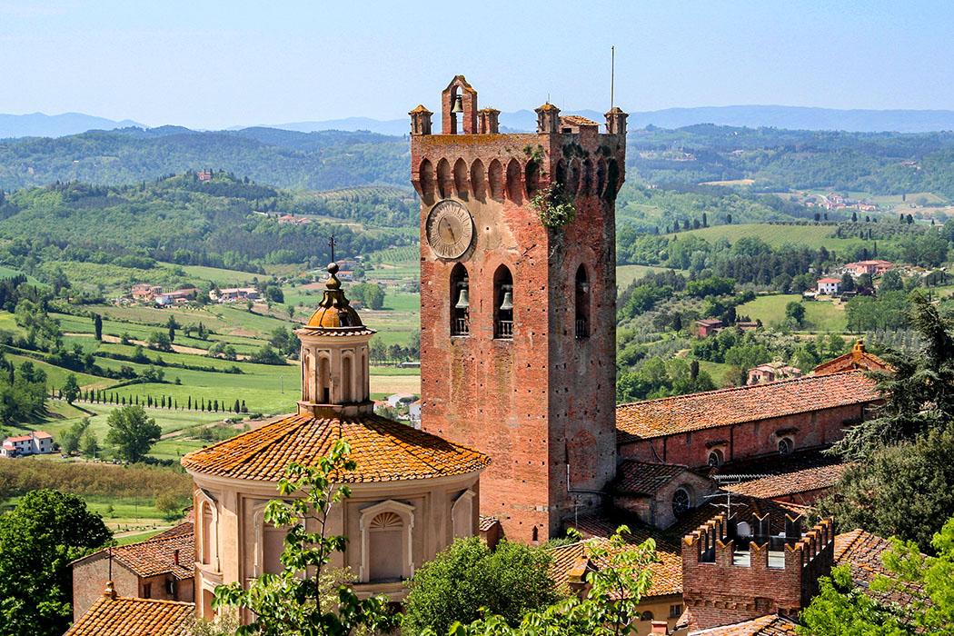 """Glockenturm des Doms (""""Torre di Matilde"""") und Kuppel der Kirche Santissimo Crocifisso, San Miniato San Miniato: Der Torre di Matilde vom Dom San Genesio. Einst diente er als Wachturm und wurde später in den Domkomplex als Glockenturm integriert. Daneben die Kuppel von Santissimo Crocifisso. Foto: Wikipedia"""