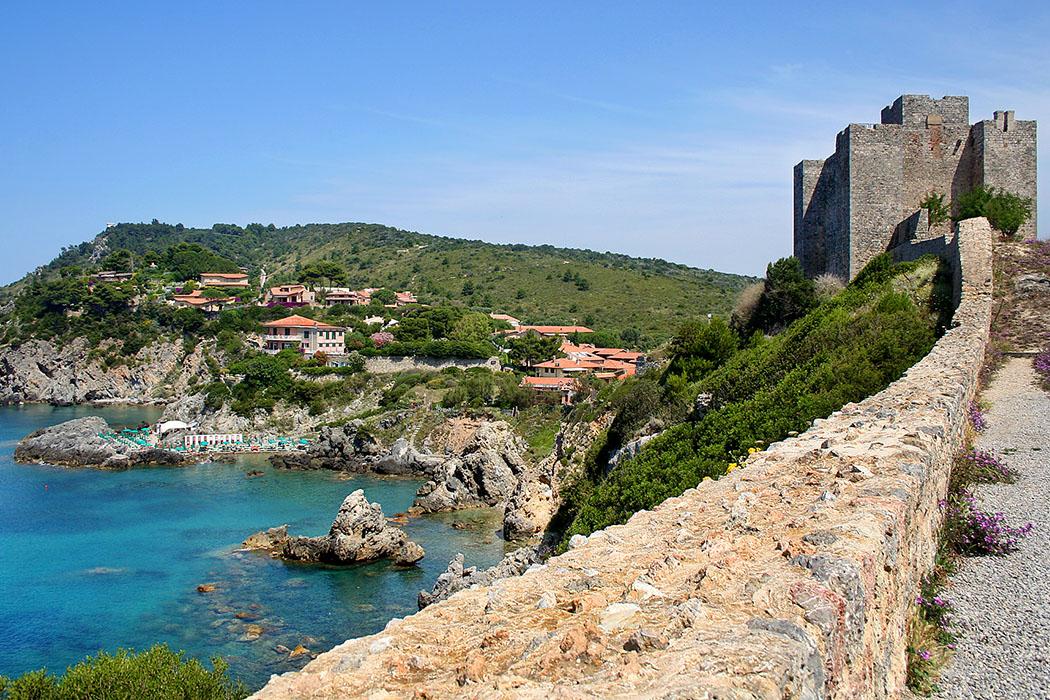 Talamone, Castello Talamone: Aussicht von der mittelalterlichen Festung der Grafen von Aldobrandeschi über die Felsenküste zum Freibad Bagno Delle Donne am Meer. Foto: Wikipedia, Roberto Ferrari