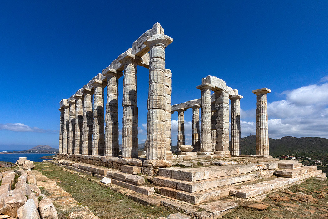 Griechenland: Attika - Der Poseidon-Tempel auf Kap Sounion Der berühmte Poseidon-Tempel auf Kap Sounion wurde von 444 bis 440 v. Chr. aus Agrileza-Marmor erbaut. Heute sind von 38 dorischen Säulen wieder 18 aufgerichtet. Foto: M. Hoffmann, Reise-Zikaden reise-zikaden.de-griechenland-kap-sounion-poseidon-tempel-panorama
