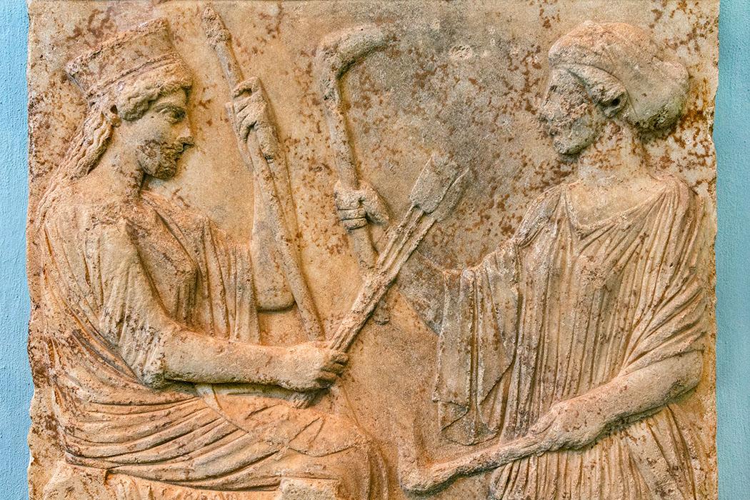 Griechenland: Attika – Eleusis und der Mysterienkult im Demeter-Heiligtum Das Marmorrelief aus dem Archäologischen Museum von Eleusis zeigt Demeter auf einem Thron sitzend. Ihr gegenüber steht Kore (Persephone) mit Fackeln in der Hand. Die Fackel ist ein Symbol der eleusinischen Weihen. Die Votivgabe an das Demeter-Heiligtum datiert auf den Zeitraum 500 bis 475 v. Chr. reise-zikaden.de, greece, attica, eleusis, elefsina, Demeter and Kore (Persephone), marble relief, 500-475 BC, Archaeological Museum
