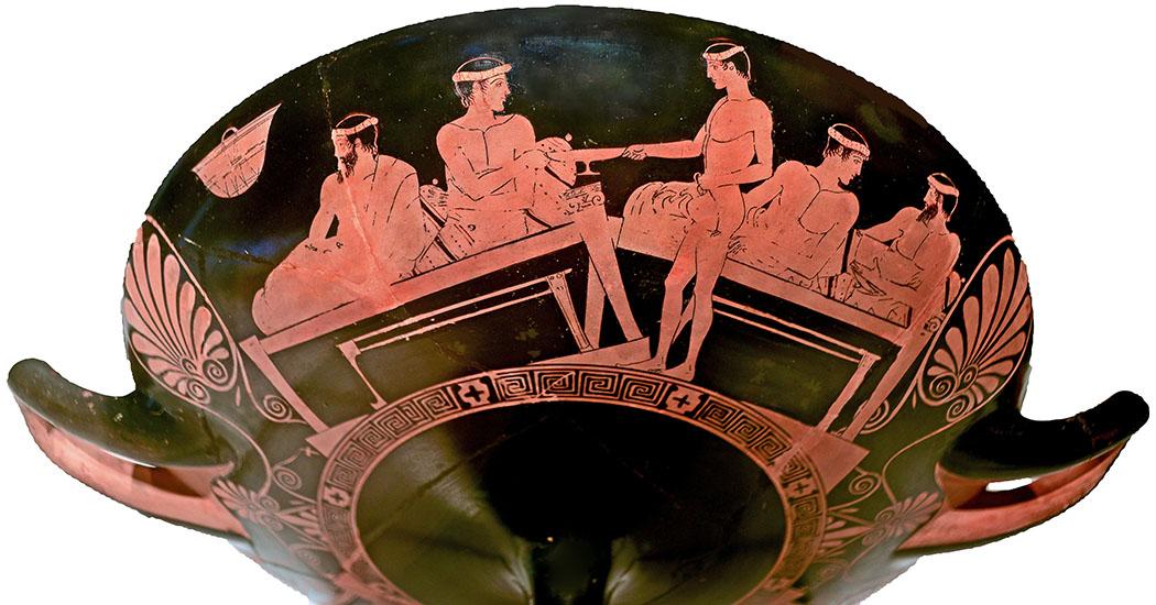 Griechenland: Attika – Weinberge und Weingüter um Athen Greek Pottery, Diese rotfigurige attische Kylix zeigt ein Symposion. Ein Diener füllt einem Teilnehmer aus einer Oinochoe Wein in eine Kylix. Datierung: ca. 460-450 v. Chr., Louvre, Paris. Foto: Wikipedia, Jastrow