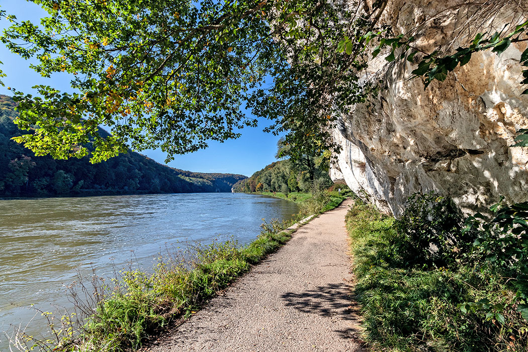 """reise-zikaden.de, deutschland, niederbayern, kelheim, kloster we Die mächtige Felswand """"Hohlstein"""" liegt etwa einen Kilometer vor der Weltenburger Enge. Um den Weg am Donauufer weiterführen zu können, musste ein Teil Felsen abgeschlagen werden. Die verwitterte Formation wird auch """"Bienenkorb"""" genannt. Foto: Reise-Zikaden, M. Hoffmann"""
