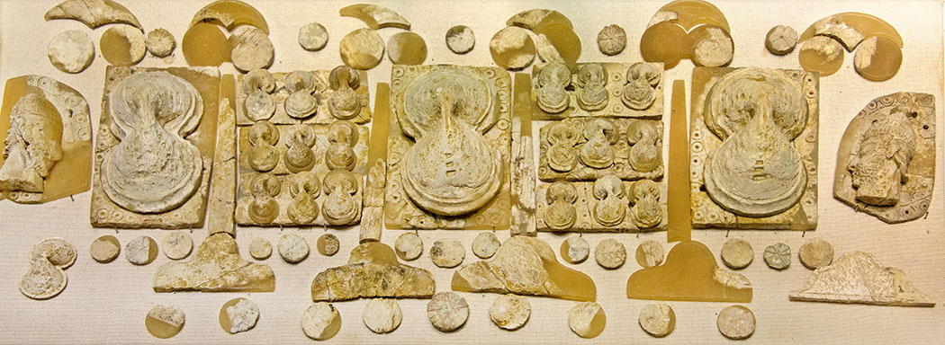 Bronzezeit auf Kreta: Krieger-Ideologien und Waffen der Minoer Ivory_inlay_plaques,_shields,_Archanes-ausschnitt Reliefartige Einlagearbeiten aus Elfenbein schmückten eine Holzkiste, die in einem minoischen Frauengrab gefunden wurde. Abgebildet sind drei Achterschilde, zwei Krieger mit Eberzahnhelm und Papyrusblüten. Fundort: Archanes Phourni Gewölbegrab A. Datierung: 1.400 - 1.350 v. Chr. Ausstellungsort: Archäologisches Museum, Heraklion. Foto: Wikipedia, Zde
