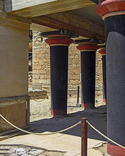 """Bronzezeit auf Kreta: Die Paläste der Minoer waren Basis ihrer Städte reise-zikaden.de, griechenland, kreta, knossos, minoer, minoische säule, kretische säule, column Ein weiträumiger L-förmiger Portikus mit rekonstruierten minoischen Säulen liegt vor der """"Halle der Doppeläxte"""" im Ostflügel von Knossos. Foto: Reise-Zikaden, J. Hoffmann"""