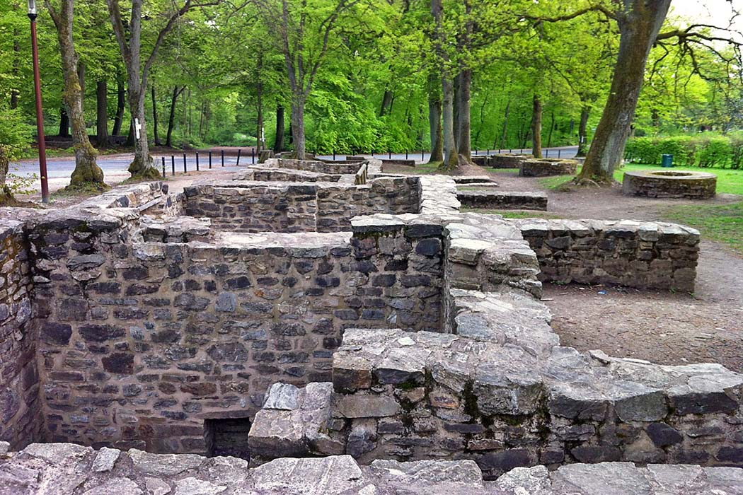 Hessen, Saalburg, Vicus Foto: Wikipedia, Xipolis Der Vicus war das Dorf um das Römerkastell Sallburg. Die Abbildung zeigt Steinfundamente und Keller, im Hintergrund liegen mehrere Brunnen. Foto: Wikipedia, Xipolis