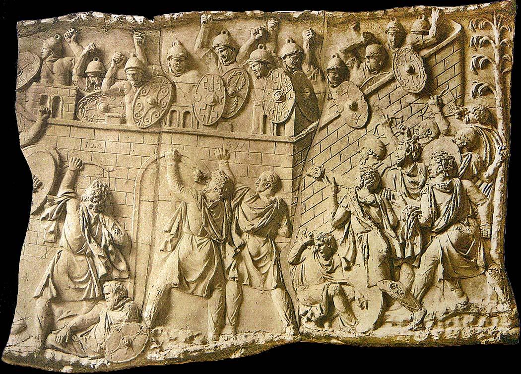 Relief_Traianssäule,_Tafel_XXIV_01 Das Relief zeigt wie dakische Kämpfer eine römische Festung belagern. Die Darstellung (Szene XXXII) stammt von der Trajanssäule in Rom. Auf dem spiralförmigen Fries werden auf einer Länge von zweihundert Metern Szenen aus den Dakerkriegen von Kaiser Trajan abgebildet. Datierung: 112/113. Foto: Wikipedia, Conrad Cichorius