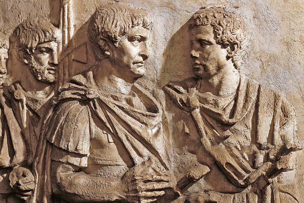 Trajans Column scene 104 sura_ol Die Abbildung von der Trajanssäule in Rom zeigt Kaiser Trajan (links) im Dialog mit Lucius Licinius Sura im zweiten Dakerkrieg 105/106 (Szene 104). Liktoren (rechts außen) halten Fasces (Rutenbündel mit Beil). Foto: www.trajans-column.org