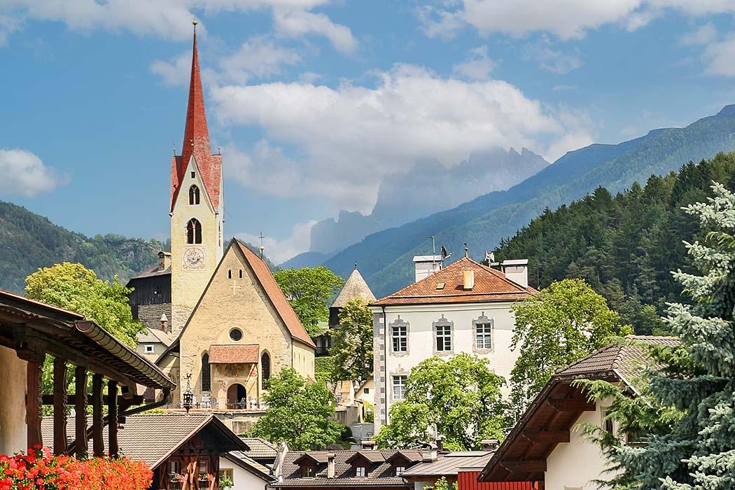 reise-zikaden.de, Südtirol, Unsere 10 schönsten Ausflüge um Brixen im Eisacktal, Gufidaun, Geisler Das Bergdorf Gufidaun liegt über dem Eisacktal und westlich des Villnösstals. Im Hintergrund sind ist das Dolomitenmassiv der Geislerspitzen sichtbar. Foto: Reise-Zikaden, M. Hoffmann