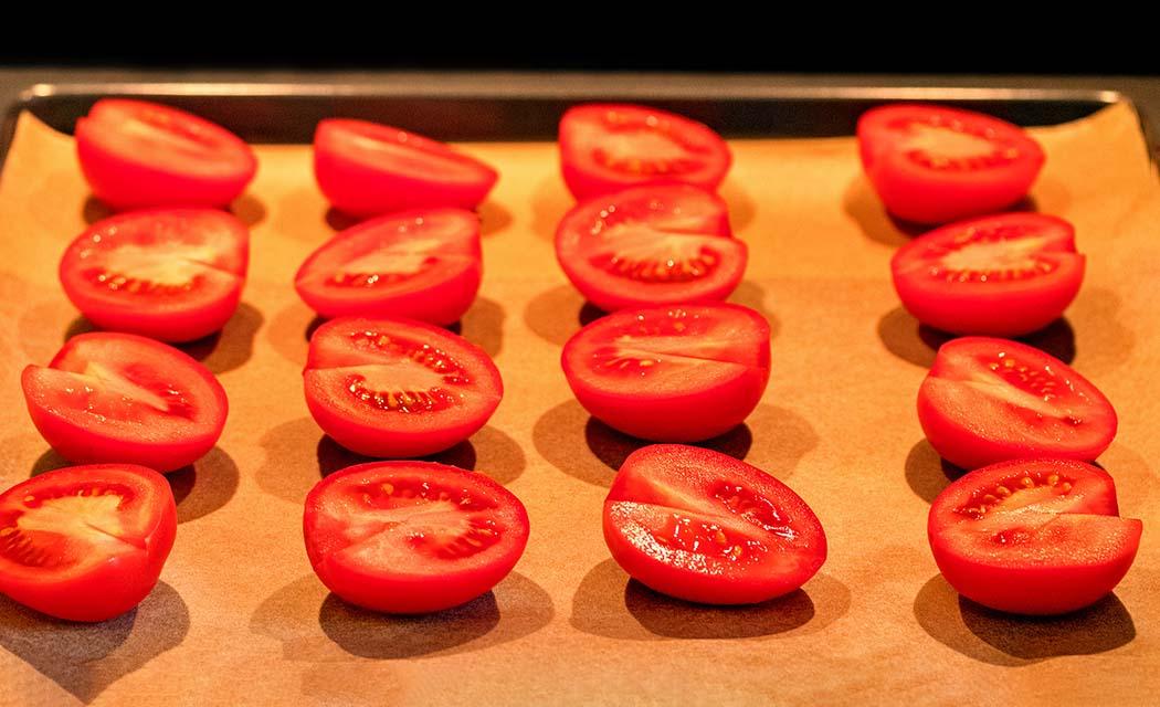 reise-zikaden.de, Pomodori secchi – Ofengetrocknete Tomaten selber machen Eiertomaten waschen, halbieren und Stielansatz herausschneiden. Dann mit der Schnittfläche nach oben auf ein mit Backpapier belegtes Backblech legen. Foto: Reise-Zikaden, M. Hoffmann